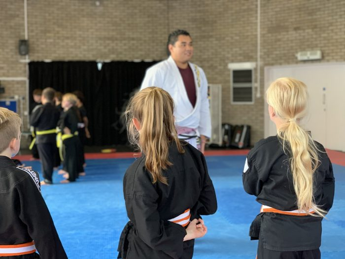 Children lined up watching martial arts coach.