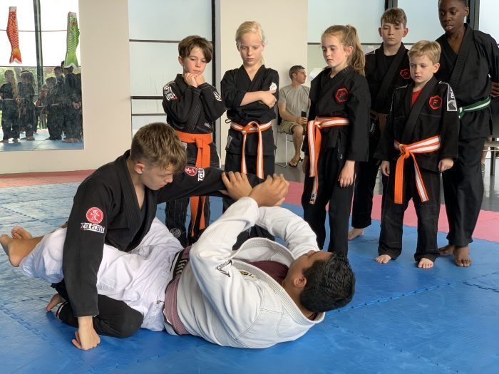 Martial arts coach teaching a small group of children.